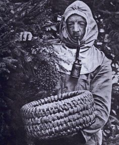 Beekeeper 1937 - blows on the smoker as he urges the bees into the skep