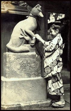 Tying Fortune on Fox -- T. Enami Ca.1915-23. Japanese girl tying a fortune on a fox statue at a temple.