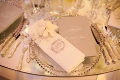 Perfection! Silver beaded glass chargers and white, light taupe linens and cards. Beautiful silverware and crystal. Simple and elegant.