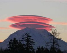 In this photo there are two clouds stacked up into one beautiful and striking lenticular cloud on top of Mt. Rainier, US.  Normally, air moves much more horizontally than it does vertically. Sometimes, however, such as when wind comes off of a mountain or a hill, relatively strong vertical oscillations take place as the air stabilizes. The dry air at the top of an oscillation m  ay be quite stratified in moisture content, and hence forms clouds at each layer where the air saturates with moisture