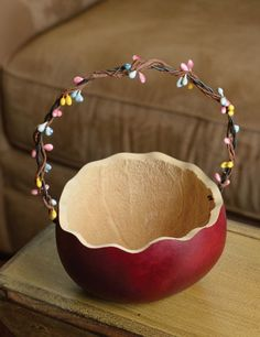 """Retired - This basket is great for sharing your Easter candy, eggs or carrots. The handle is decorated with spring colored berries and the basket has a scalloped edge. It is red in color and approximately 5"""" in diameter."""