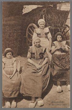 2 Vrouwen met gehaakte muts strak over hoofd, zonder kuif, kleine gesteven kraplapjes, voorste in lichtpaars. Lichte rouw, en hele rode doek, geruite boormouwtjes. Achterste vrouw draagt wit schort, voorste schort met donker geruit bovenstukje en klompen met leertje. Linker meisje draagt pluummuts en over kraplap lieffiessjullek, het rechter meisje een pluummuts, een kraplap met de hele rode doek en een schort met geruit stukje. Beide dragen witgeschuurde klompen. 1910-1920 #Utrecht…