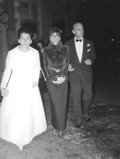 The actress Audrey Hepburn photographed (with unknown friends) after a gala dinner in Rome (Italy), in December 1968.Audrey was wearing:Evening gown: Norman Norell (one shoulder, sleeveless, of black crepe, at the waist a belt lined with the same tissue with a golden buckle ornamented as a brooch, of his collection for the Autumn/Winter 1968/69).