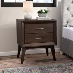 With its clean-lined design and on-trend mod appeal, this essential two-drawer nightstand is a perfect partner for your preferred platform bed. Made from manufactured wood and Asian hardwoods in a rich coffee finish, this charismatic design showcases a simple square silhouette with midcentury modern-inspired flared legs. Two dovetail drawers with steel drawer pulls offer plenty of space for you to store a booklight, notepad, tablet, and a lockbox for valuables, while the flat top provides a…