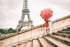 So romantic Paris engagement picture in the rain. Red umbrella, kissing in the rain in front of the Eiffel Tower.