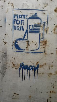 Mate for USA. Mate drink and hot water thermal bottle. San Cristobal, Buenos Aires, Argentina. Stencil on metal door.
