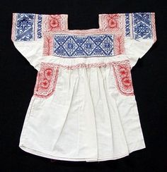 "Woman's blouse (""blusa bordada"" in Spanish); made of factory-made white calico/cotton cloth; red machine-stitched embroidery around neck, at bottom of yolk, on underarms and along side seams; blue hand embroidery (pepenado in Spanish) along yoke and on sh"