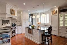 Transitional kitchen features carved wood white cabinetry doors, with modern steel appliances, black countertops, and an immense brick tile backsplash surrounding the range area. Luxury Kitchen Design, Kitchen And Bath Design, Luxury Kitchens, Cool Kitchens, Kitchen Decor, White Kitchens, Beautiful Kitchen Designs, Best Kitchen Designs, Beautiful Kitchens