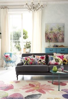 Bring summer blooms into your home with an abundance of gorgeous floral cushions on your sofa. Team with an equally vivid rug on a white painted floor and let the light flood in with plain linen curtains. Photography: Mark Scott. Find more living room ideas at housebeautiful.co.uk