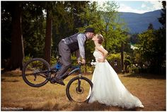 Groom on mountain bike kissing bride, photographed by Chuck Hocker of Etched Productions. www.etchedproductions.ca