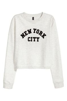 Printed sweatshirt: Top in light sweatshirt fabric with a print motif, long sleeves and ribbing around the neckline, cuffs and hem. The top is in a slightly shorter, wider style.