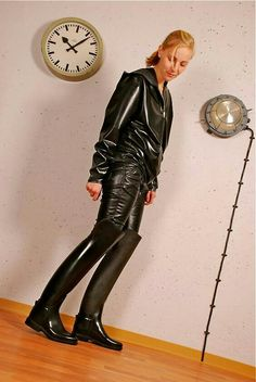 Amateur blonde in shiny black leather jacket, pants, and OTK riding boots