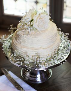 How amazing is this homemade two tier buttercream wedding cake, complete with delicate babys breath and flowers on top.