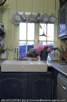 Country kitchen with teacups instead of curtains. Cute!