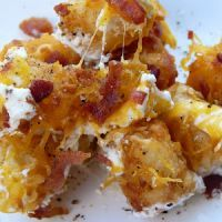 Cheesy Ranch Tater Tots ~ 1 bag frozen tater tots ;  1 C sour cream ;  1/2 C ranch dressing ;  1/4 cup milk ;  1 C  Shredded cheddar cheese ;  1/2 C shredded mozzarella cheese ;  1/2 C real bacon bits