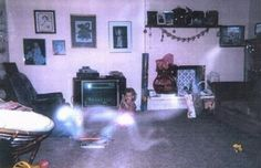 A father took this photograph of his young daughter playing in their living room and was surprised to see this ghostly, crawling form of light energy in front of her. It also looks like the child can see it too.
