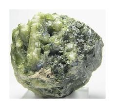 Green Tourmaline Crystals growing out of big by FenderMinerals