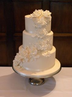 Elegant ivory wedding cake with a cascade of handmade roses,  blossom and butterflies.  www.littleascakery.co.uk