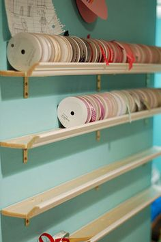 Inexpensive and easy Ribbon Storage: Flat part of the shelf is baseboard material and the lip is made from crown molding.  Just glued together with wood glue.