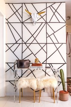 Raquel used black tape to make the pattern on this wall. And these stools were originally bright orange from IKEA, but Raquel spray painted them gold and added a sheepskin from Etsy to the top. The acrylic console is from CB2. The steer head was found at HomeGoods.