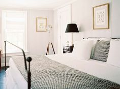 A black and white bedroom with checkered polka dot like pillow and blanket on the black iron bed.  I like the subtle touches of gold in the room too. http://cococozy.com