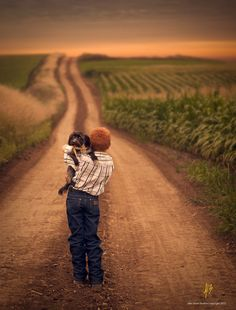 a boy, a dog, a dirt road, and a corn field. what more do you need