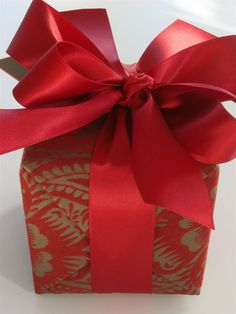 Red All Over | Use lots of beautiful satin ribbon to embellish your gift wrapping - Carolyne Roehm #giftwrapping #red #emballagecadeau