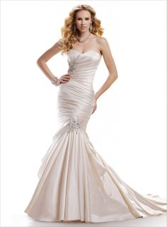 Maggie Sottero Sydney - This L'Amour Satin fit and flare hugs every curve with asymmetrical pleating creating a lean silhouette. Featuring beaded motifs with Swarovski crystals and finished with strapless sweetheart neckline and signature corset closure.