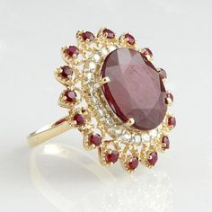 Lady's 14K Yellow Gold Dinner Ring, with a 14.88 carat oval ruby atop a diamond mounted border within a pierced outer border of round rubies, total ruby wt.- 16