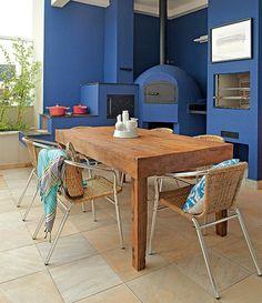 Com forno a lenha e churrasqueira, a varanda ficou mais vibrante com as pinceladas azuis. A mesa de madeira de demolição também faz diferença na decoração. Projeto da arquiteta Andrea Murao