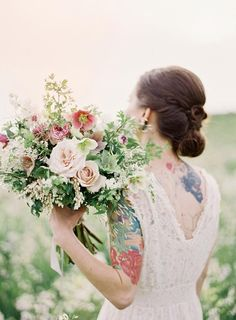 bride with tattoos on her arm and shoulder carries large bridal bouquet