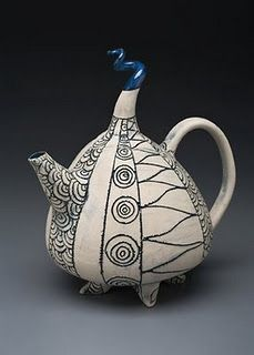 black bird sitting on top of a teapot