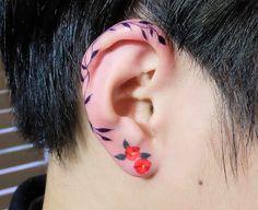 Koreli dövme sanatçısı Zihee'nin, kulak kıkırdağını saran bir asma ve küpe gibi duran iki çiçekten oluşan eseri.