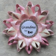 Planning a baby shower? This pretty corsage can be custom made for your guests! Choose the wording for the center piece. Each flower is handmade from satin ribbon in Pale Pink, Ivory and Quartz. The flower is 3 1/2 inches wide with a bar pin backing and and comes packaged in a gift