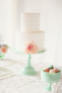 Simple cake with mint stand and pink flower accent.