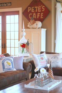 Sugar Pie Farmhouse living room; rustic farmhouse, vintage farmhouse; white furniture, red sign, feedsack pillows; flags & flowers