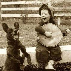 A young boy playing the banjo with his dog, circa 1920