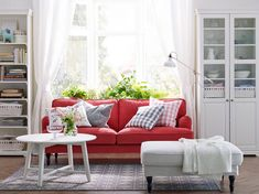 A white living room with a red STOCKSUND sofa, LIATORP cabinet and bookcase in white,  storage in calm white.