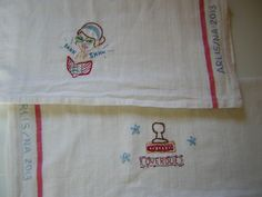 """""""Clean Like a Librarian"""" Dishtowels. Two dishtowels, hand-embroidered with librarian-themed images, and an ARLIS/NA 2013 memento. Created and donated by Dayna Holz."""