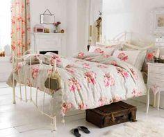 literie florale et lit en fer forgé blanc dans la chambre romantique