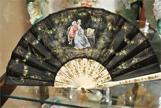 ITEM # 614101   Vintage, circa 1940s, French hand painted ( I looped it) black silk fan with a carved gold floral celluloid handle.   The scene is of lovers or a courting couple in a garden, sitting on a bench.   Back is stamped in gold Made in France.   Very good vintage condition with very little wear typical to age and handling. One of the sticks in the back has a tiny piece of paper torn, upon very close inspection a couple of tiny frays and I found 2 tiny pin holes.   Fan measures 11…