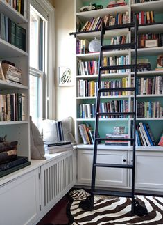 Library with white built-in shelving, pop of color, and a rolling ladder.  At home with the Editor of This Old House magazine - NYTimes.com
