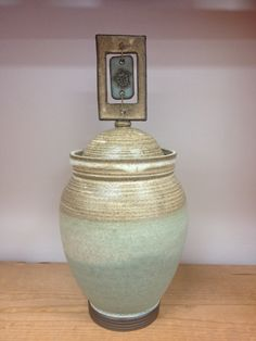 Large jar with turtle in window attached with hemp rope. Stoneware pottery