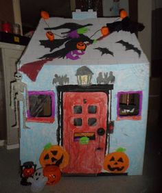 Cardboard Halloween house for kids. It's a great DIY project to get the kids involved in painting and decorating.