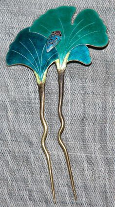this beautiful hair pin depicts two Gingko leaves with a bug. It's made with cloisonne enamel.