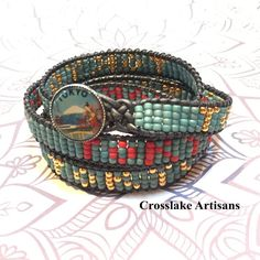 I love vintage buttons. The inspiration for this four-wrap bracelet is a vintage style Intaglio button of Tokyo. I chose three colors from the button... turquoise, red and gold. The base of the wrap is the turquoise and Ive repeated Tokyo in red and gold around the entire wrap. For a perfect fit, you can email me with yur wrist measurement. Without this information, you will receive an average size wrap which is 28 inches long and fits a wrist of 6-6.5 inches.