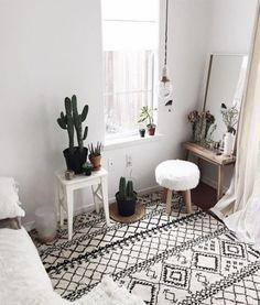 Zen apartment with graphic carpet, furry stool & cactus plants