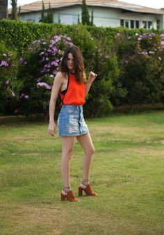 Denim mini skirt, orange top, and brown sandals