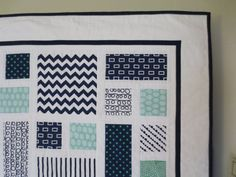 This baby quilt features about 10 different cottons in navy, mint and white, solids and geometrics, randomly scattered on a field of Kona white. Its crisp contrasts in color and pattern make it a whimsical and lively quilt. Freehand overall quilting by machine. Made to order. Backing is solid Kona white.    40 x 40 is a perfect size for your babys tummy time, crib, cuddle time, or play mat. Machine wash separately, cold, gentle cycle, mild detergent. Tumble dry low. Recommend using Shout…