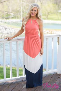 This new maxi is to die for! It has our favorite colorblock style in coral, white, and navy with halter straps that tie in the back and an elastic band around the waist!